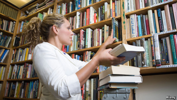 A librarian putting up books