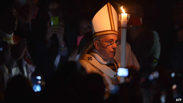 Pope Francis carries a candle at Easter vigil ceremonies in Rome