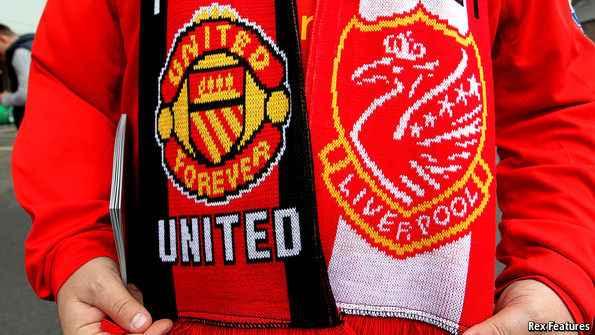 Football supporter with scarf showing Manchester United and Liverpool badges