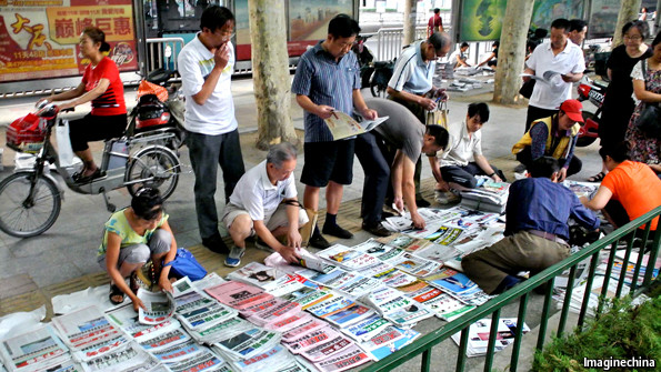 People viewing newspapers laid out on a pavement
