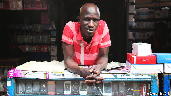 Man in Mali leans on his table of mobile phones