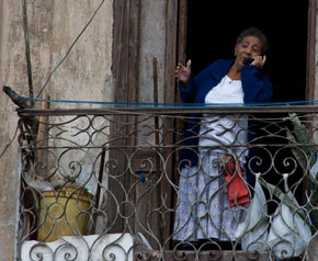 A woman on a mobile phone in a balcony in Havana