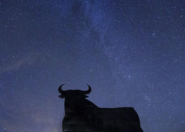 Звезды и метеоры Персеид полоса по небу над силуэтом придорожного рекламного щита испанского боевого быка в Reduena