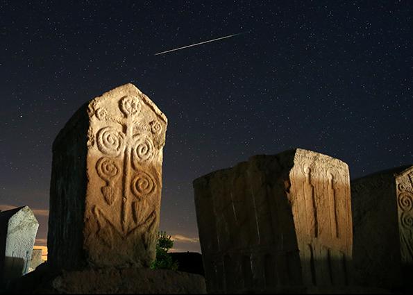 Метеорный след среди звезд в ночном небе над средневековых надгробий в Radmilje, недалеко от Столаца, Босния и Герцеговина