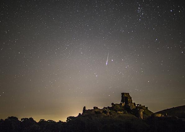Метеорные вспышки Персеид в ночном небе над замка Корф, Дорсет, Англия