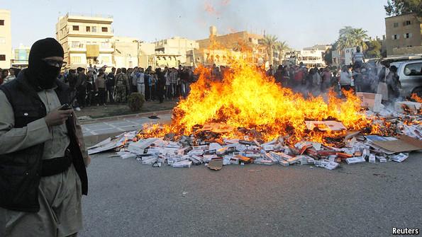 عناصر داعش يحرقون المئات من علب السجائر